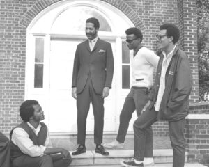 4 men standing in front of Gates Hall